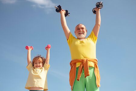 Grandfather helping kid exercising with dumbbells. Senior man and child in family health club. Father and son spotting.
