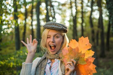 Happy autumn girl wink, Ok. Autumn outdoor atmospheric moments and dream. Autumn and leaf fall Dreams. Autumnal mood.
