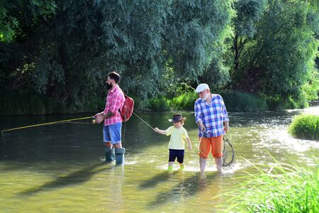 Fly fisherman using fly fishing rod in river. Grandpa and grandson are fly fishing on river. Great-grandfather and great-grandson. Reklamní fotografie - 128235002