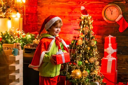 Merry christmas and happy new year. Cute little child boy play near christmas tree. Kid enjoy winter holiday at home. Home filled with joy and love. Best wishes for you your family this christmas