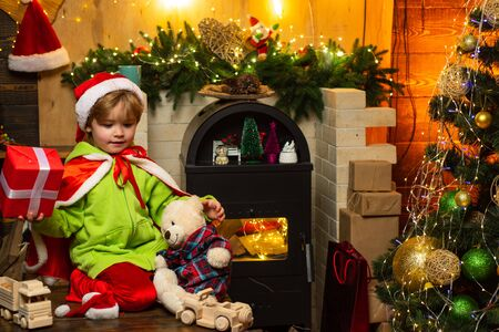 Home filled with joy and love. Make wish. Best wishes for you your family this christmas. Merry christmas and happy new year. Cute boy play near christmas tree. Kid enjoy winter holiday at home