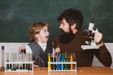 Back to school - education concet. Happy smiling pupil and teacher drawing at the desk. Father teaching her son chemistry or biology in classroom at school