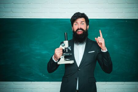 Serious male Student studying in school. Young bearded teacher near chalkboard in school classroom. Teachers day - knowledge and educational school concept. Education.
