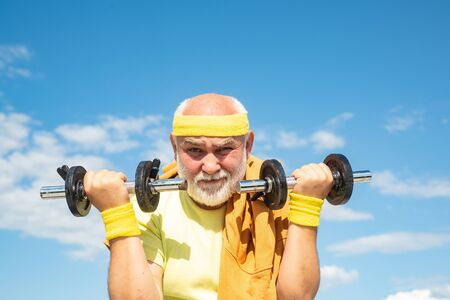 Old sportman exercising with lifting dumbbell on blue sky background. Isolated, copy space. Reklamní fotografie