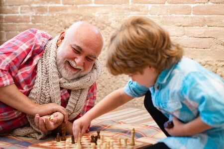 Cute little boy playing chess. Childhood. Cute little boy playing chess. Generations. Handsome grandpa and grandson are playing chess while spending time together at home.