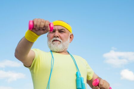 Senior male is enjoying sporty lifestyle. Elderly man practicing sports on blue sky background. Elderly man after her workout. Senior man in health club.