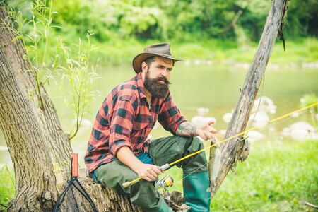 Fly fishing in the pristine wilderness of Canada. Happy fisherman fishing in river holding fishing rods. Stock Photo