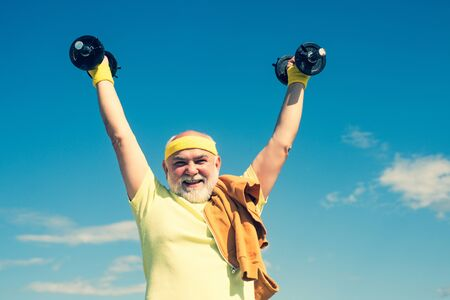 Senior man in health club. Be in motion. Age is no excuse to slack on your health. Elderly man practicing sports on blue sky background. Stok Fotoğraf