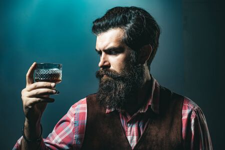 Sad man with depression looking in camera. Drunk man holding whisky glass after he drank a lot of alcohol and feeling headache. Reklamní fotografie