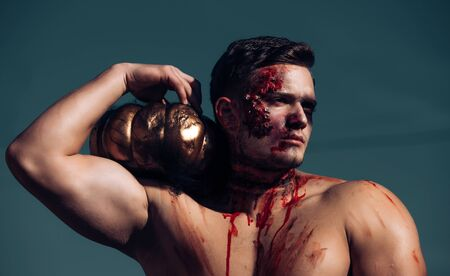Big zombie man halloween vampire or bloody war soldier with wounds and red blood with pumpkin. Death - young man Halloween portrait. Halloween man with pumpkin in the street. Sport and health food.