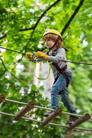 Child concept. Rope park - climbing center. Hike and kids concept. Go Ape Adventure. Happy Little child climbing a tree.