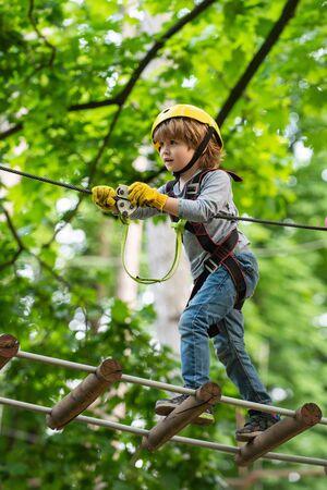 Child concept. Rope park - climbing center. Hike and kids concept. Go Ape Adventure. Happy Little child climbing a tree. 版權商用圖片