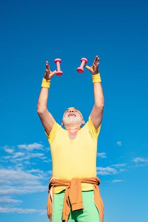 Senior male is enjoying sporty lifestyle. Body care and healthcare. Senior man exercising on blue sky. Old mature man exercising with dumbbell.