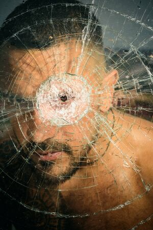 damage. hispanic man broken mirror. anger. destruction. crush test. theft. emotional discharge. bullet hole in glass. broken glass because of hit. macho man behind crushed glass, damage