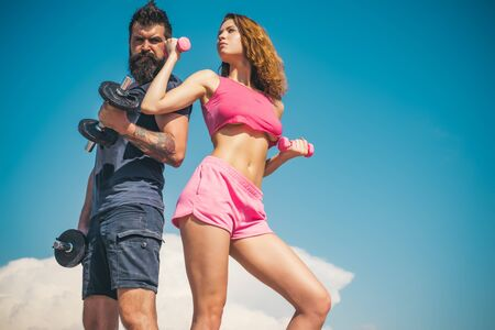 summer activity. barbell equipment. sporty couple training outdoor. perfect body muscle. healthy lifestyle. dieting. freedom. dumbbell lifting. sport and fitness. bearded man and woman with fit belly