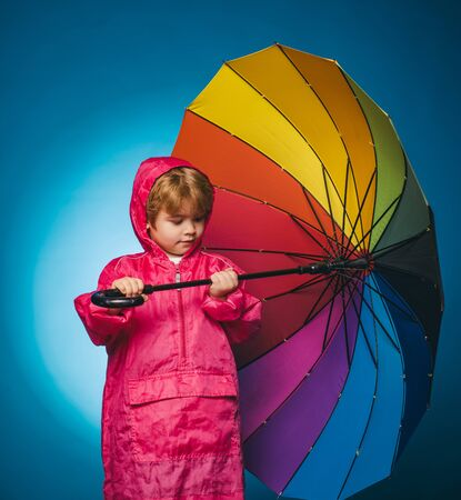 Cheerful boy in raincoat with colorful umbrella. Raining kids. Child advertise your product and services. Cloud rain umbrella. Biggest discounts for all autumn clothes for children. Raining concept.