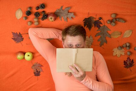 Red-haired man lies on an orange background and eats an apple. The big discounts for all autumn clothes for men. Young cute man lies on a wooden floor with autumn leaves and read book. Banco de Imagens