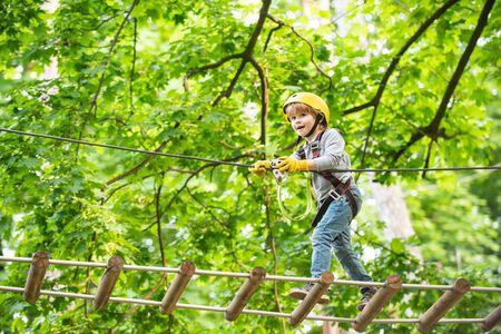 Rope park - climbing center. Child boy having fun at adventure park. Go Ape Adventure. Child boy having fun at adventure park