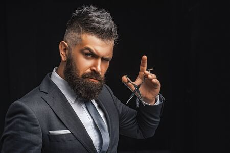 Barbershop concept. Mature hipster with beard. bearded man in formal business suit. brutal male hipster cut hair with hairdressing scissors. confident businessman at barbershop. barber and hairdresser salon