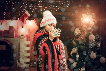 Happy little girl dressed in winter clothing think about Santa near Christmas tree. Winter kids. Kids Christmas. Christmas story concept. Christmas kids.