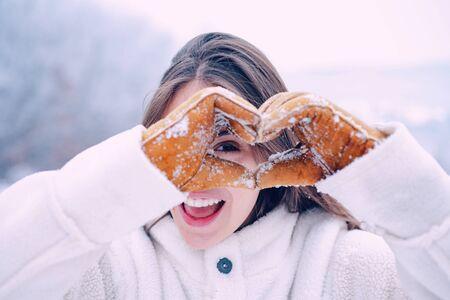 Winter woman. Happy winter woman show snow heard. Outdoor beautiful girl. Winter holidays. Snowfall. Banco de Imagens