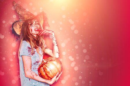 Halloween-Frauendesign. Halloween-Mädchen mit einem geschnitzten Kürbis. Schöne junge überraschte Frau im Kostüm, das Kürbis hält. Halloween-Hexe mit Kürbis. Standard-Bild