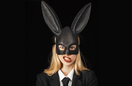 Sexy woman with mask Easter bunny on a black background and looks very sensually. Closeup of winking bunny girl face. Sexy woman wearing a mask Easter bunny and looks very sensually.