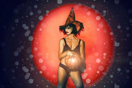 Halloween woman design. Romantic girl with pumpkin on red light background. Wonam murderers hold pumpkin. Fashion nude Art design. Standard-Bild