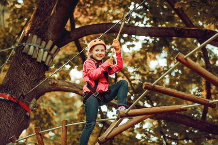 Hike and kids concept. Toddler kindergarten. Eco Resort Activities. Happy child boy calling while climbing high tree and ropes. Children summer activities.