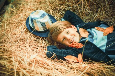 Autumn Clothing and color kids trends. Boy on a breeze in an autumn village. Autumn child boy with autumnal mood. Advertisement concept.