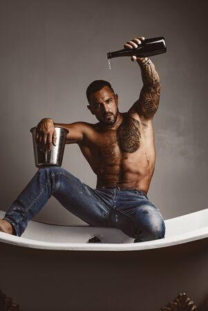 Loisirs d'élite de luxe. Un concept de vie de luxe avec bouteille de champagne. Homme brutal avec une bouteille de champagne qui se déverse dans le bain. Vie luxueuse. Hommes attirants avec de l'alcool d'élite de luxe.