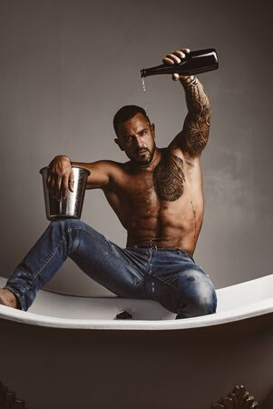 Luxury elite leisure. A concept of luxury life with champagne bottle. Brutal man with a bottle of champagne which pours into the bath. Luxury life. Attractive men with luxury elite alcohol. Banque d'images