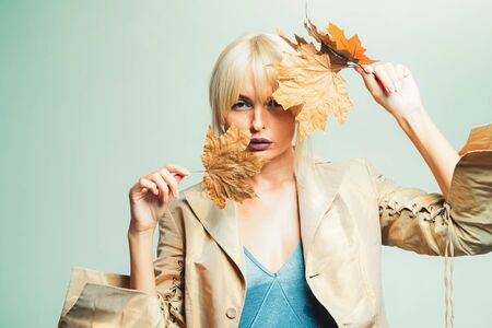 Happy young woman are preparing for autumn sunny day. Beautiful girl with background board for Copyspace. Attractive young woman in a seasonal clothes whith golden leaf. Beautiful sensual blonde. Stock Photo