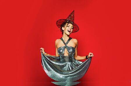 Gelightful blonde lady dressed in a fashionable dress on red background. Halloween dresses and witch costumes design. Best ideas for Halloween. Glam costumes of party people. Stock Photo