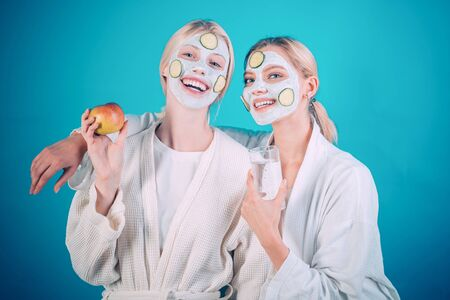 Girls friends sisters making clay facial mask. Anti age mask. Stay beautiful. Skin care for all ages. Women having fun cucumber skin mask. Drink water eat fruits. Health concept. Spa and wellness