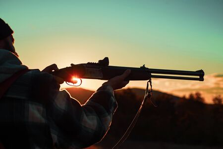 Hunter man. Barrel of a gun. Rifle Hunter Silhouetted in Beautiful Sunset. Hunter with Powerful Rifle with Scope Spotting Animals. Copy space for text.