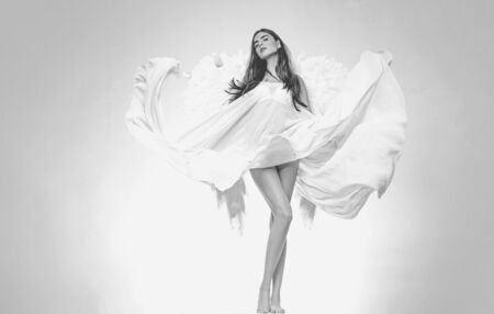 Angel girl. Beautiful fairy flying girl in white dress. Angel woman with wings isolated. Stock fotó