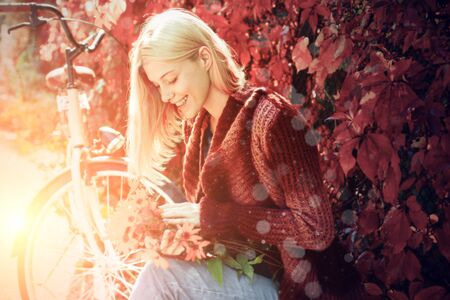 Happy girl on autumn walk. Beautiful happy smiling blonde girl with long hair wearing stylish jacket posing in autumn day. Autumn Clothing and color trends. Stock Photo