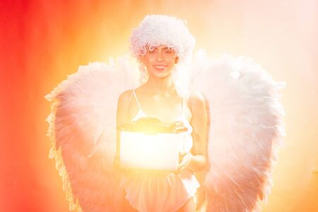 Angel with gift. Art photo of a Angelic beautiful woman. Angel woman with feather white wings and gift. Love concept.