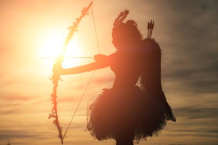 Silhouette of a cupid. Side view of teen girl archer against sunset. Cupid in valentine day - Valentine concept.