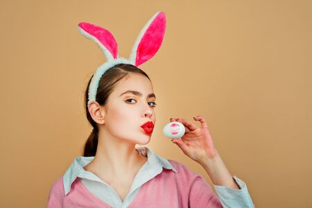 Easter, Lipstick kiss imprint on easter egg. Happy easter. Young woman in rabbit bunny ears. Portrait of a happy woman in bunny ears. Egg hunt.