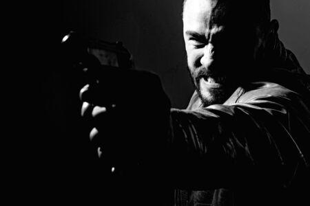 Killer or murderer concept. Mafia killer going to shot someone. Finish him. Kill them all. Final shot. Concentrate on gun shot. Need for revenge. Close up gun barrel