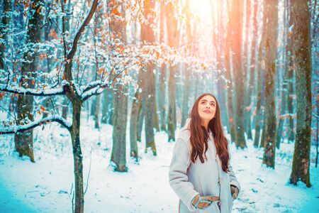 Girl having fun in winter park. Winter portrait of young beautiful brunette woman in snow Garden.