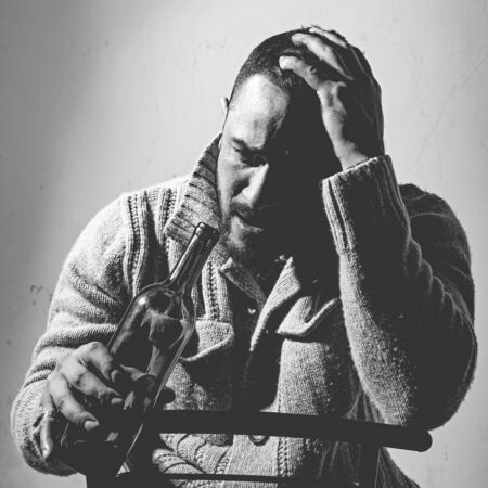 Alcohol addiction and people concept. Frustrated man with bristle is holding his head, crying and sitting with a bottle in his hands. Depression. Disorders of health.