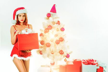 Sensual girl with Christmas box gifts. New year party. White background. Christmas gifts for sexy woman. New year santa girl. Imagens