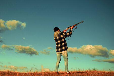 Hunter in the fall hunting season. Hunter with shotgun gun on hunt. Skeet shooting.