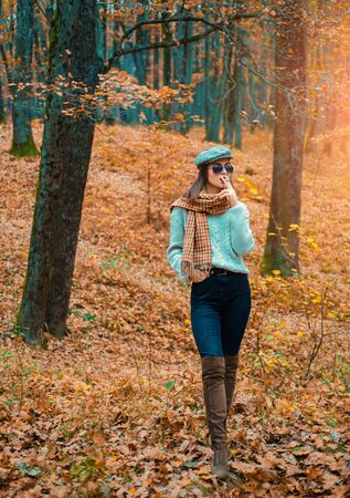 Autumn woman. Fashionable model wearing warm brown boots and cap in the forest. Resting from noisy city concept.
