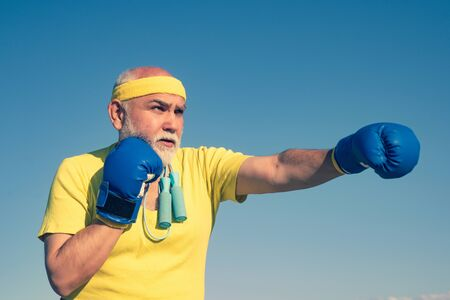 Boxing. Portrait of a determined senior boxer over blue sky background. Senior man wearing boxing gloves. Boxer with boxing glove. Reklamní fotografie - 128418045