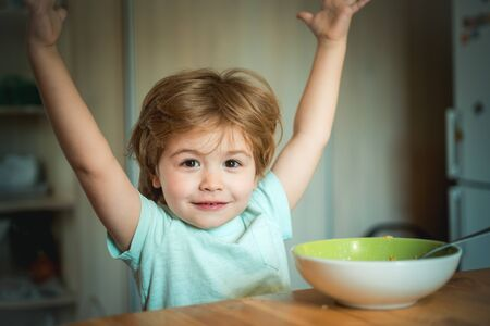 Baby eating food on kitchen. Kid boy eating healthy food at home. Young kid sitting on the table eating with funny expression on face. Summer ration. Childcare. Excited Stock fotó