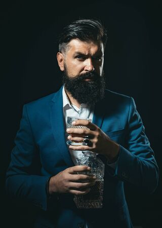 Handsome bearded businessman is drinking expensive whisky. Sommelier man.